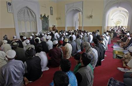 Afghan men listen to a Muslim cleric delivering sermons during Eid-al-Fitr prayers inside in Kabul